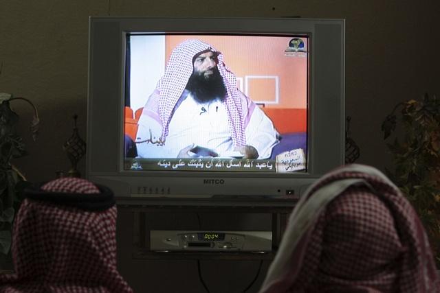 Saudis watch a religious program in Riyadh
